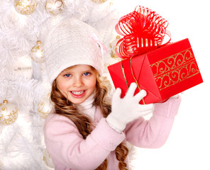 Child in hat and mittens holding  Christmas gift box .