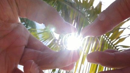Wedding Rings in Hand against Palms and Bright Sun. Slow Motion.