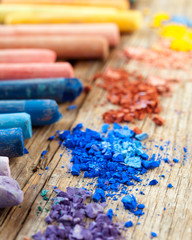 Collection of rainbow colored pastel crayons with crushed chalk.