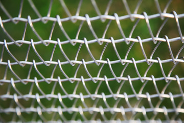 Closeup of wire mesh fence with green background