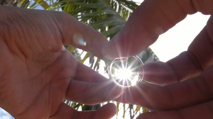 Two Gold Wedding Rings in Hands on Beach with Palm and Sun.