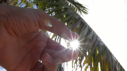 Groom Hand Holding Wedding Ring against Palm and Sky.