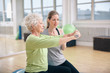 Senior woman training in the gym with a personal trainer - 74365692