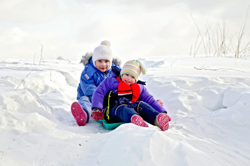 Two girls on sled in winter