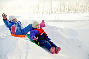 Two little girls on sled through the snow to slide