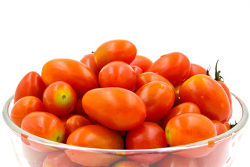 Cherry tomatoes in a glass bowl on white background.