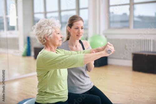 Leinwandbild Motiv Senior woman training in the gym with a personal trainer