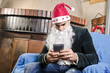 Young man with Santa costume sending sms to friends