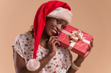 African Christmas woman wearing Santa Claus hat holding gift