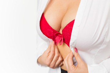 Woman with big breasts wearing red bra and white shirt