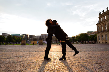 Afrikanischer Mann umarmt Freundin in der Innenstadt