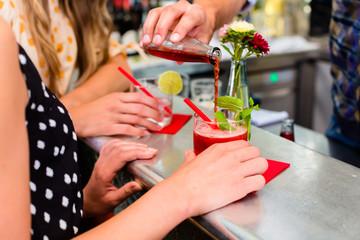 Zwei Freudinnen in Bar trinken Longdrink