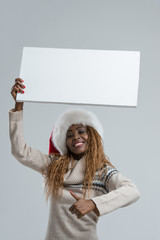 Young african woman in Santa Claus hat holding sign