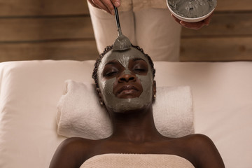Professional applying mud mask to african woman