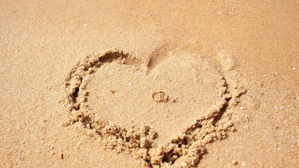 Wedding Rings in Sand Heart on the Beach with Sea.