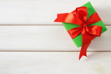 Green gift with red ribbon on a wooden table