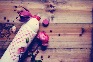 Pink rose with bottle on a wooden background