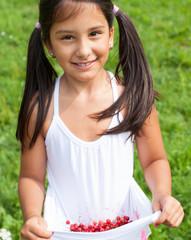 Mädchen trägt frisch gepflückte Johannisbeeren in ihrem Hemd