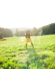 Mädchen in gelbem Kleid spielt Ball
