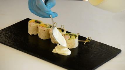 Professional chef hands with pieces of wheat cake or roll filled