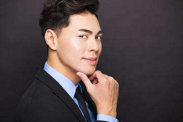 Smiling businessman standing on black background