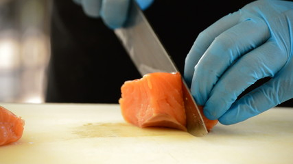 Professional chef hands cutting a salmon fillet