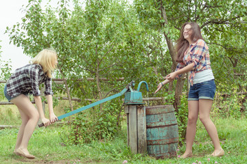 Girls splashing water from village hand pupm