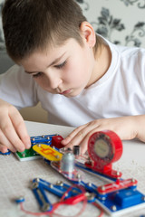 Teen boy at home with electronic project