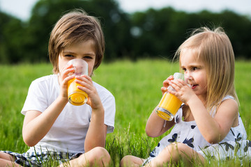 Little girl and boy drink juice