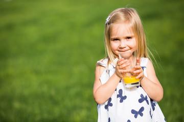 Little girl drink orange