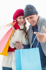 Happy couple in warm clothing with shopping bags
