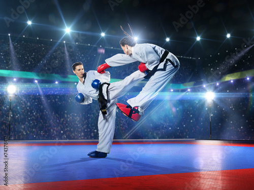 Two professional female karate fighters are fighting - 74378412