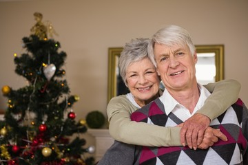 Senior couple smiling beside their christmas tree