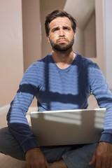 Depressed man sitting on floor using laptop