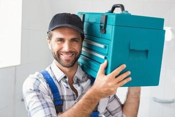 Plumber holding toolbox on shoulder
