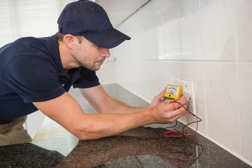 Electrician working at plug socket