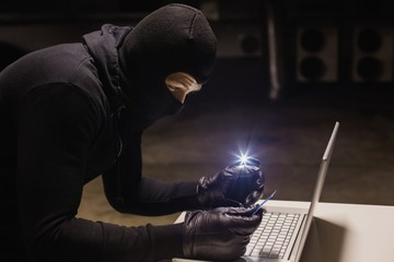 Robber shopping online while making light with his phone