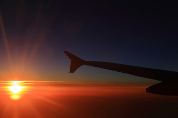 Sunset sky and airplanes wing view out of the window