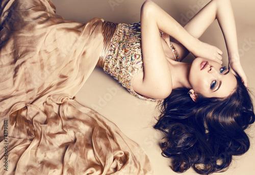 beautiful brunette in luxurious sequin beige dress