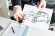 Salesman holding a key and showing a car design