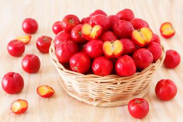 Malpighia glabra (red acerola), tropical fruit  in wicker busket