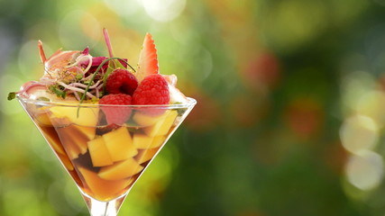Cocktail cup glass with strawberry, mango and wine