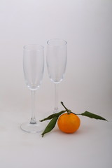 Still-life with wine glasses for champagne and a tangerine
