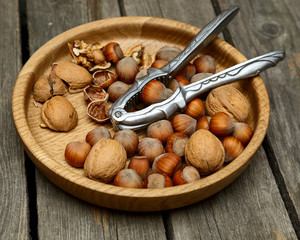 Hazelnuts, walnuts  in a wooden bowl on a gray table