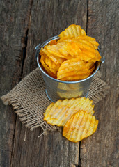 potato chips in a bucket on wooden surface
