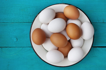 Chicken eggs in a metall dish on the blue boards