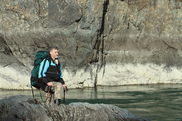 The traveler with a backpack and tracking sticks at the river