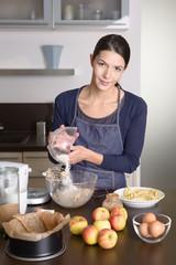 Junge Frau backt in der Küche einen Kuchen