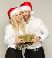 Beautiful couple with presents wearing santa claus hat