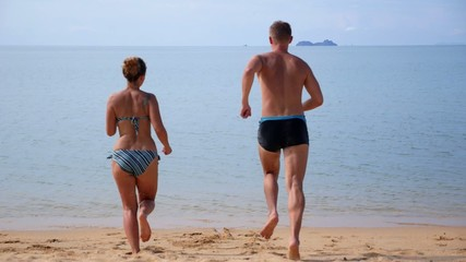 Couple Enjoying their Vacations and Splashing in Sea. Slow